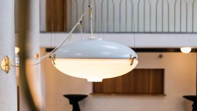 Tefatsliknande lampa i vitmålad metall och frostat glas. Hänger över källaren
