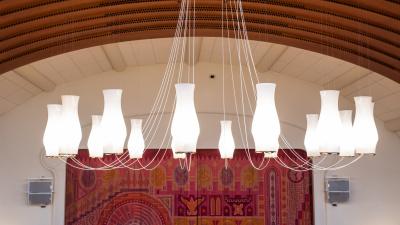 Ljuskronan i A-salen som svävar högt upp i taket. Den består av 15 avlånga glaskupor i frostat opalglas, som sitter i en cirkel på varsin tunn metallarm.