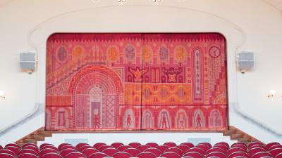 Ridån till A-salen är vävd i rosa, röda och orangea toner. Den innehåller olika symboler.